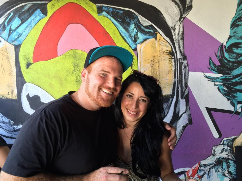 Man and woman smiling in front of colorful wall