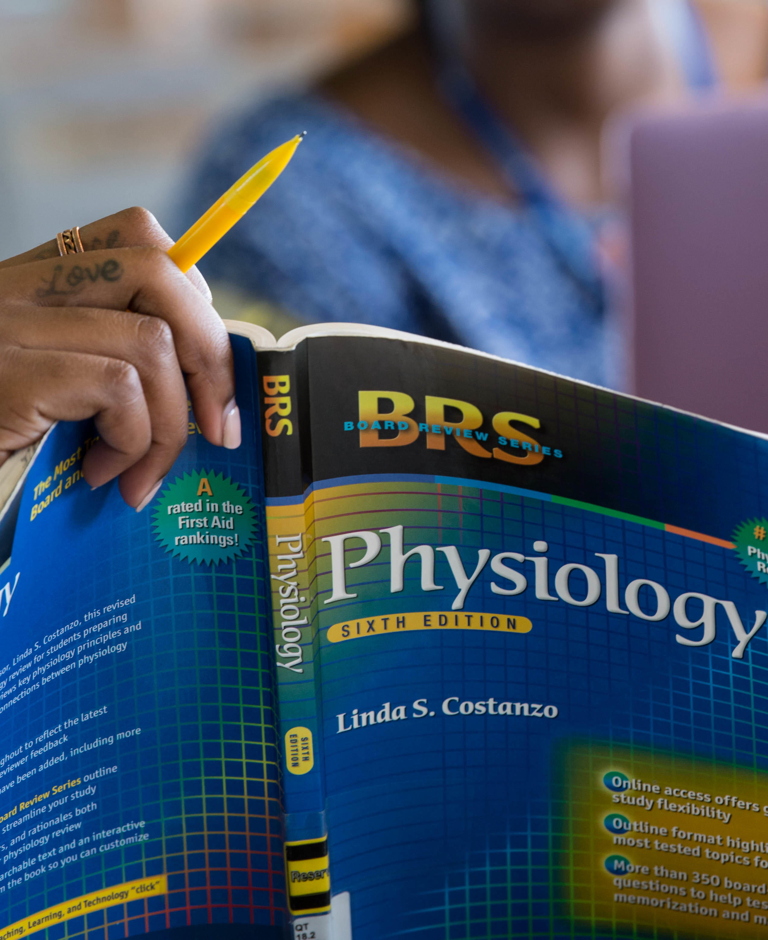 Student holding physiology textbook